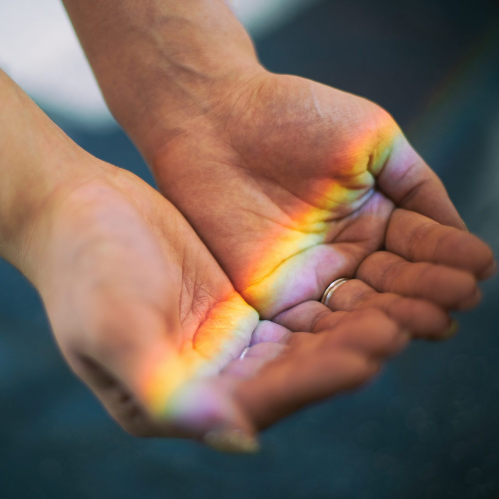 High Angle View Of Rainbow Lights Falling On Hands