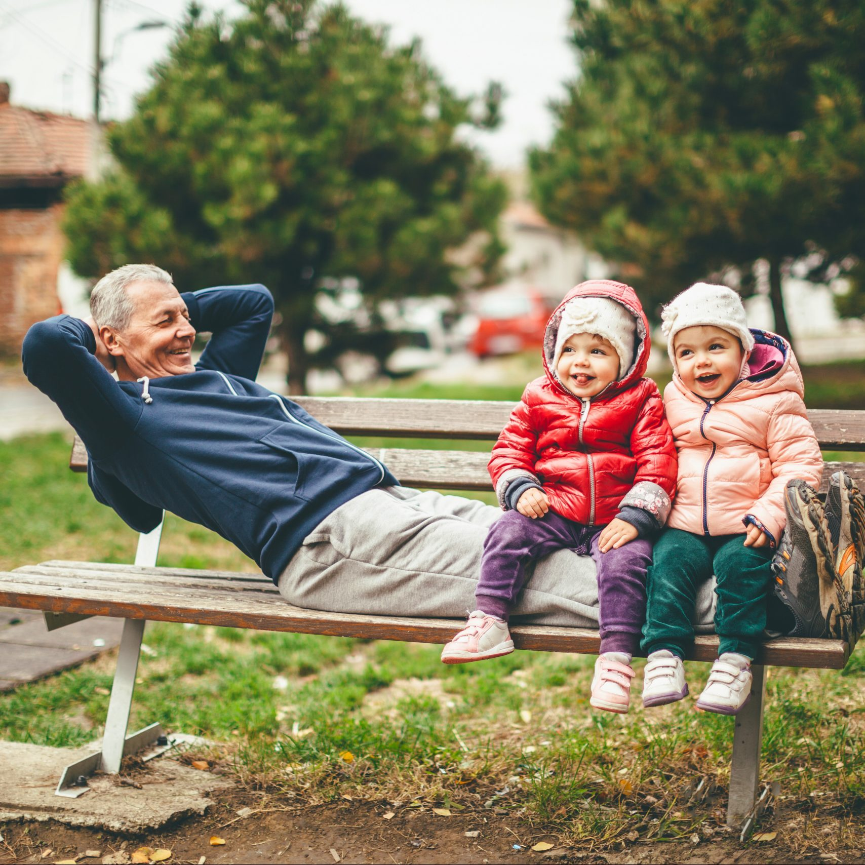 A photo of a playful grandfather and granddaughter. They are casually dressed and playing in the park. They exercise together.